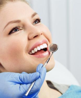 Dentist checking patient teeth looking in dental mirror. Oral procedure concept.